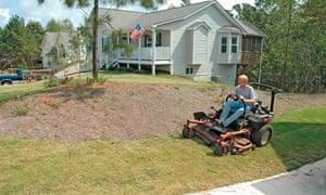 A man cuts his yards lawn ridding a mower