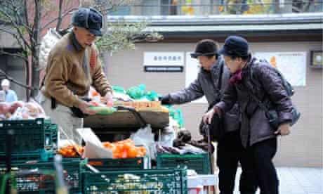 Ageing population in Japan : Elderly women choose vegetables at Kouganji Temple in Tokyo