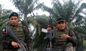 Soldiers partol a palm plantation , Honduras