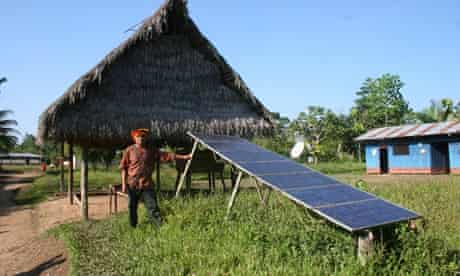 MDG : Peruvian standing next to a solar panel given by Euro-Solar Programme in Peru