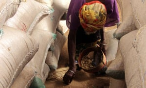 MDG : Food crisis in Niger : A woman picks spilled maize among sacks of grain