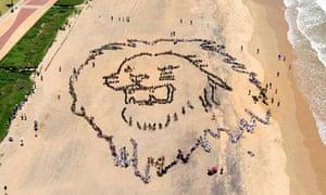 COP17 in Durban : thousands of South African youths forming a giant lion head on a beach in Durban