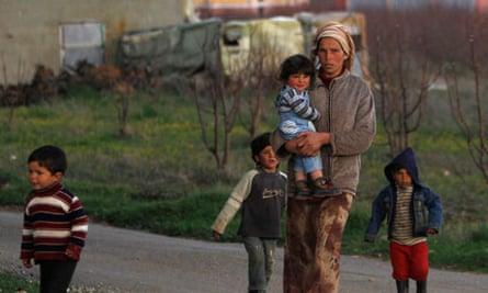 MDG : International Women's Day : Syrian woman Khadija walks with her children, Lebanon