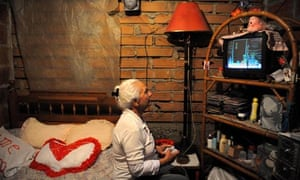 MDG : Poor economics : An eldery woman plays a video game in shantytown , Colombia