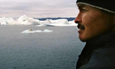Inuit fisherman looks for seals from an island near his home town of  Ilimanaq, Greenland, Arctic
