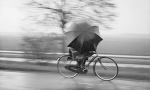 Bike blog : A cyclist sheltering from the rain underneath a huge umbrella