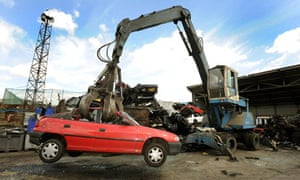 A giant mechanicial grabber lifts a car in the air to be crushed