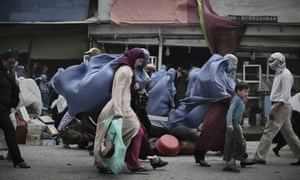 Burqa-clad MDG : Women in Afghanistan : Afghan women walk against the wind  in central Kabul