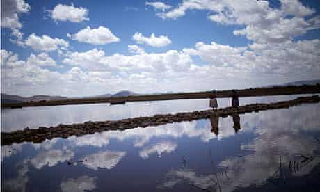 Lake Titicaca : Aymara women cross a bridge of rocks on the shores