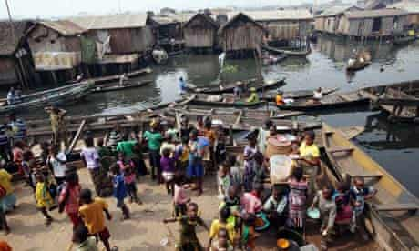 MDG : Taxation to achieve MDG : School children receive food on the waterfront of the Makoko slum