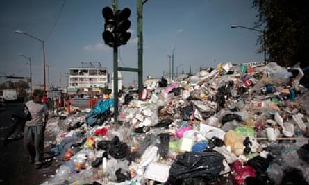 Garbage and landfilll in Mexico city : People walk past piled up rubbish in downtown Mexico City