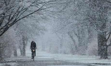 Bike blog : A young woman rides a bicycle under heavy snowfall