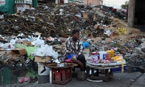 MDG : Haiti and poverty : A woman sells food next to a pile of rubbel and rubbish in Port au Prince