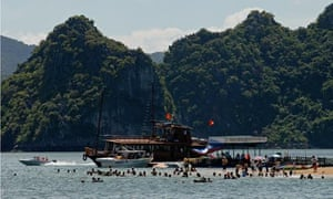 Tourists flock a tiny beach on the edge of a stone island of Halong Bay, Ha long Bay