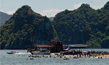 Tourists flock a tiny beach on the edge of a stone island of Halong Bay, Ha long Bay