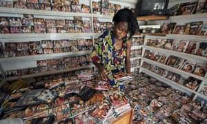 MDG : Nollywood : girl sorts through dvds in a shop at Nigerian film market in Lagos, Nigeria