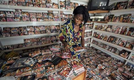 MDG : Nollywood : girl sorts through dvds in a shop at Nigerian film market in Lagos, Nigeria