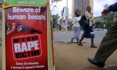 MDG : Rape in Kenya : People walk past a poster bearing a message against rape on street of Nairobi
