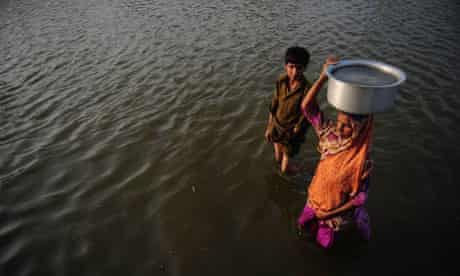 MDG : Water : A Pakistani woman carries drinking water in floods water , Pakistan