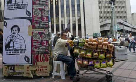 MDG : Medellin in Colombia : A peddler stays by posters with the image of drug lord Pablo Escobar
