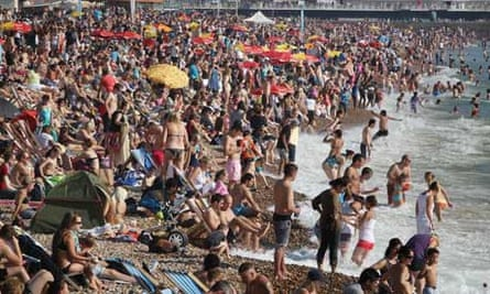 Over-consumption and over-population : Crowds of sun seekers fill the beach