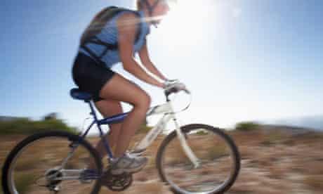 Bike blog : Woman mountain biker cycling across extreme terrain in bright sunlight