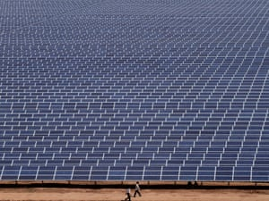 Indian workers walk past solar panels at the Gujarat Solar Park at Charanka in Patan district In India