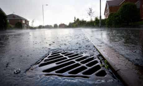 Sewage : Rainwater flowing down a drain at the side of a road