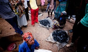 MDG : Market in Rwanda : A group of women sell charcoal on a dirt streets of Kigali, Rwanda