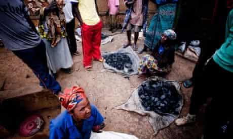 MDG : Market in Rwanda : A group of women sell charcoal on a dirt streets of Kigali, Rwanda