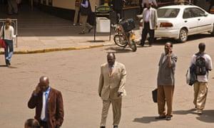 MDG : Africa growth : Kenyan use mobile phone as they walk in street in Nairobi, Kenya