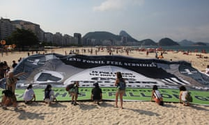 Members of Avaaz and 350 unfurl a giant trillion dollar bill on Copacana beach ahead of the Rio+20