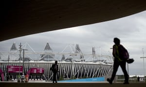 People walk past the Olympic Stadium ahead of the London 2012 Olympic Games at the Olympic Park