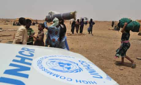 MDG : Humanitarian response to crisis : Refugees from northern Mali walk past a UNHCR car