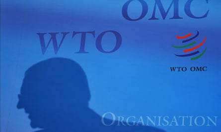 MDG : WTO : A silhouette of an official is seen with a logo of the World Trade Organization