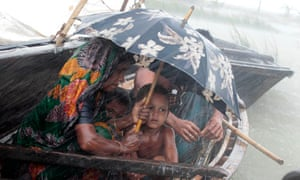 MDG : Bangladesh : Monsoon floods : A woman sits with her child in a boat during heavy rains