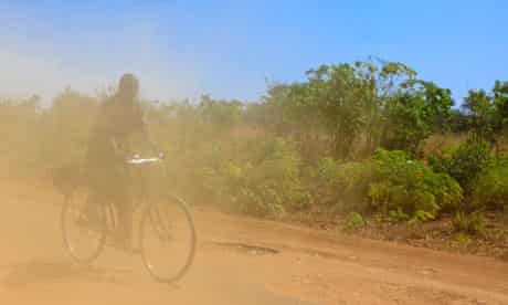MDG : Zambia : Men riding his bike in the dust on a road