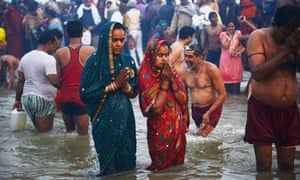 Hindu devotees pray as they bathe in the Sangham during the Kumbh Mela in Allahabad