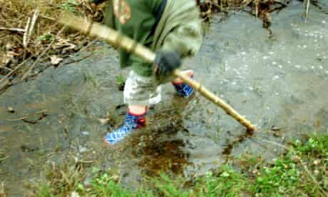 Few UK children connected to nature : Child playing in a stream in a forest in Autumn
