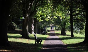 People enjoy the sun as the trees take on their autumn colours in The Royal Victoria Park in Bath