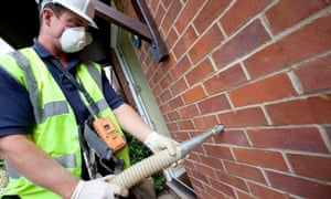 Cavity wall insulation : A worker from Total Insulation Solutions pipes Rockwool into a wall cavity.