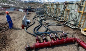 A worker helps monitor water pumping pressure for fracking (shale gas)