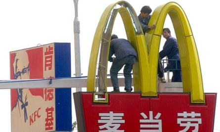 MDG :  Chinese workers install lights on a McDonald's sign in Beijing