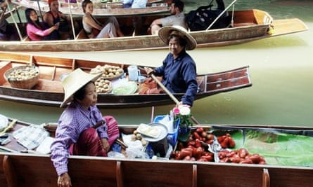 MDG : Tourist boats cruise past Thai villagers selling fruits on a canal