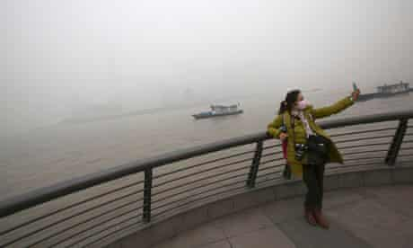 Air pollution in Shanghai, China : Tourist with protective masks visit the Bund in dense haze