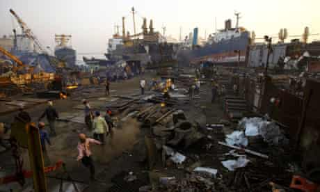 Indian workers breakdown ship parts at a ship breaking yard in Mumbai, India