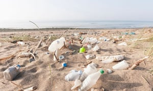 Sea plastic pollution : Plastic bottles and other rubbish washed up on a beach