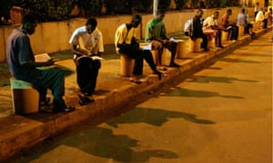 MDG : Energy poverty : students reading on parking lot lights at G'bessi Airport in Conakry, Guinea