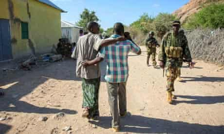MDG : Somalia conference in London : Somali civilians walk past Ugandan soldiers from AMISOM