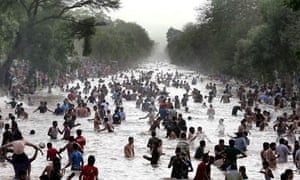 Heatwave in Pakistan :  Pakistani men and boys cool off at a canal in Lahore